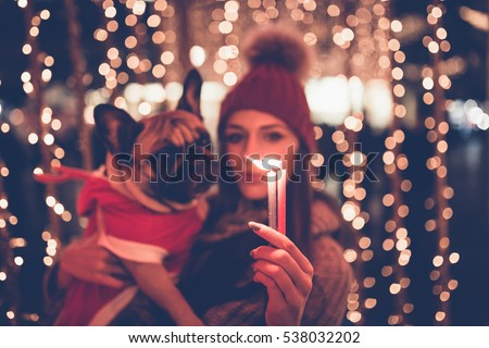 beautiful young brunette woman with french bulldog enjoying christmas or new year night on a city