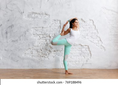 Beautiful young brunette woman in green pants and top makes an exercise for stretching legs in the gym on white brick wall background and looking into the distance. Copy space