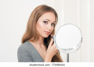 Beautiful young brunette woman in heavy elegant makeup.