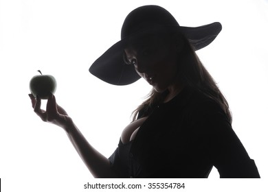 beautiful young brunette woman lady posing in a studio on a white background with old style hat biting a green apple