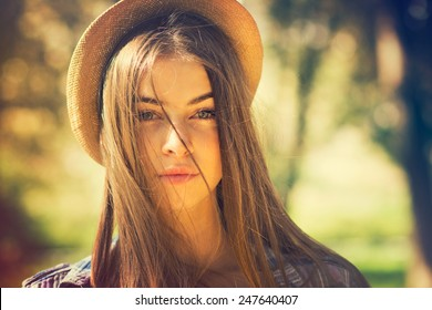 Beautiful young brunette woman with long hair flying in the wind and brown hat in park in summer. Head shot of gorgeous teenage girl with blue eyes. Retouched, filter, shallow depth of field.