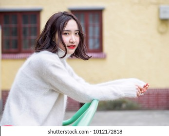 Beautiful young brunette woman looking at camera with blur house background. Outdoor fashion portrait of glamour young Chinese cheerful stylish lady, emotions, people, beauty and lifestyle concept.