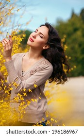 Beautiful young brunette woman near yellow flowering bushes in spring park