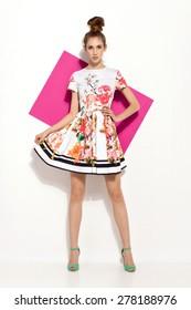 beautiful young brunette woman in nice colorful summer dress, high heels, bun, handbag posing in studio. Fashion photo