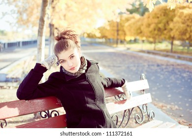 Beautiful young brunette woman on a bench in autumn