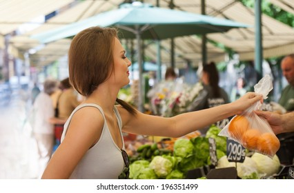 Beautiful young brunette woman on a market getting fresh food.