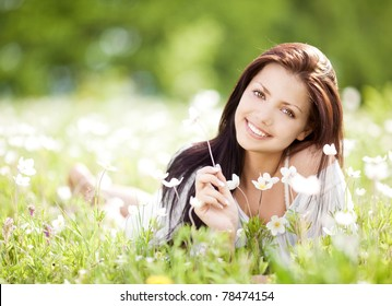beautiful young brunette woman  on the  meadow with white flowers  on a warm summer day