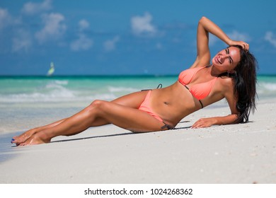 Beautiful young brunette woman in orange bikini swimsuit is smiling on tropical sand of Caribbean sea coastline at summer sunny day