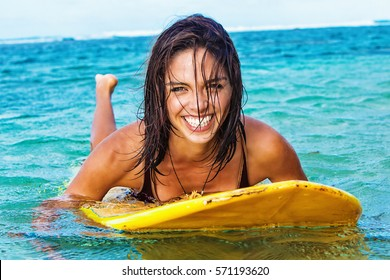 Beautiful young brunette woman paddling belly-down on her yellow surfboard in Hawaiian waters with a bright smile on her face