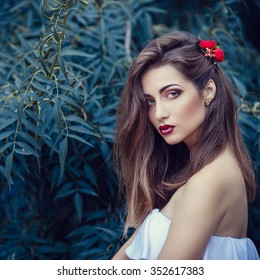 beautiful young brunette woman in a Park at sunset with flower wreath. summer time