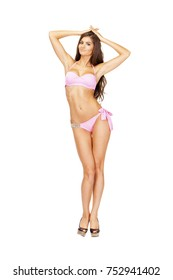 Beautiful young brunette woman in pink swimwear standing in full growth and isolated on white background