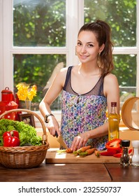 Beautiful young brunette woman preparing healthy food in the kitchen.
