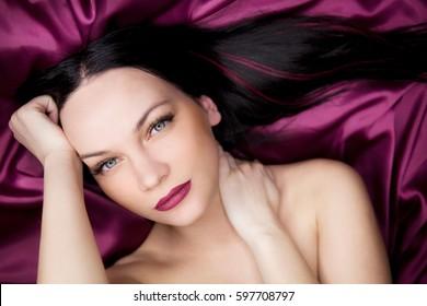 Beautiful young brunette woman with purple lips on purple silk. Close-up portrait.
