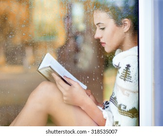 Beautiful young  brunette woman reading book wearing knitted dress sitting home behind a window covered with rain drops. Blurred fall garden reflection on the glass. Raining autumn concept