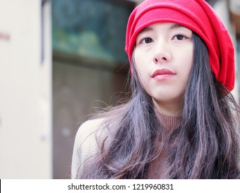 Beautiful young brunette woman in red headscarf sitting and looking aside daydreaming. Outdoor fashion portrait of glamour young Chinese stylish lady. Emotions, people, beauty and lifestyle concept.