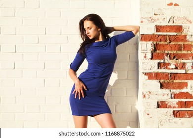 Beautiful young brunette woman in sexy blue dress, against white brick wall, summer outdoors