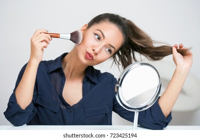 Beautiful young brunette woman in simple makeup with mirror.