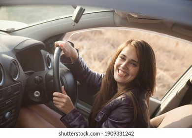 Beautiful young brunette woman sitting inside of modern car. laughing latina hispanic girl sitting on the driver's seat behind the wheel