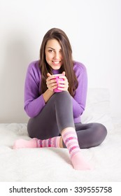 Beautiful young brunette woman sitting in bed at home holding a cup of coffee or tea. Happy teenage girl relaxing drinking hot beverage, wearing loungewear smiling. Medium retouch.