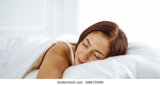 Beautiful young brunette woman sleeping while lying in bed comfortably and blissfully. Good morning concept