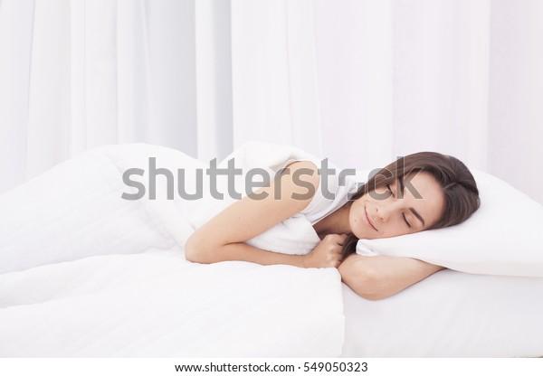 白いベッドで眠る美しい若いブルネットの女性。