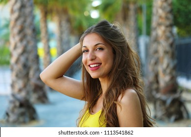 Beautiful young brunette woman smiling with perfect smile in a park waiting for someone