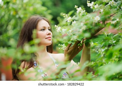 beautiful young brunette woman standing near the flowered tree