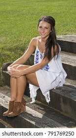 Beautiful young brunette woman standing in white dress sits on wooden stairs
