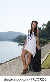 Beautiful young brunette woman standing in white dress along path near river with large suitcase