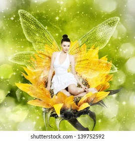 Beautiful young brunette woman as summer fairy on sunflower