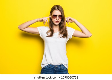 Beautiful young brunette woman in sunglasses covering her ears with her hands, isolated on a yellow background
