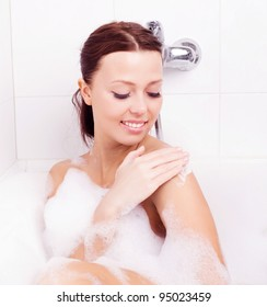 beautiful young brunette woman taking a relaxing bath with foam