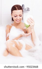 beautiful young brunette woman taking a relaxing bath with foam and using shampoo into her palm