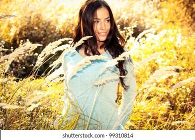beautiful young brunette woman walking through sunny yellow autumn field