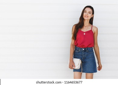 Beautiful young brunette woman wearing denim mini skirt, pink cami top, small white bag, gold rings and necklace standing near white roller door. Trendy casual summer or spring outfit. Street fashion.