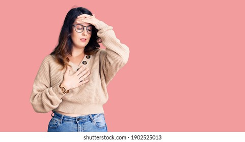 Beautiful young brunette woman wearing casual clothes and glasses touching forehead for illness and fever, flu and cold, virus sick