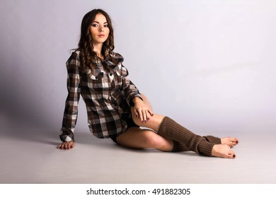 beautiful young brunette woman wearing a plaid shirt and gaiters
