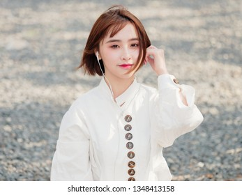 Beautiful young brunette woman in white shirt sit and enjoy music in sunny day. Outdoor fashion portrait of glamour Chinese cheerful stylish girl, emotions, people, beauty and lifestyle concept.