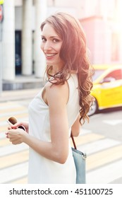 Beautiful young brunette woman in white dress on crosswalk background