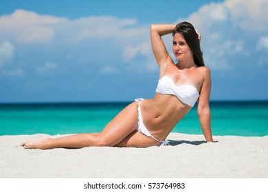 Beautiful young brunette woman in white bikini is posing on the sand of caribbean sea at summer sunny day