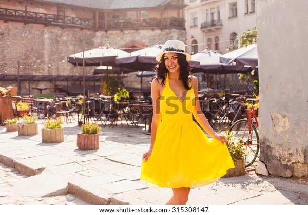 古い町の通りにある黄色いドレスと帽子を着た美しい若いブリュネットの女性