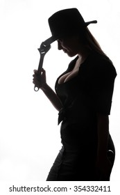 beautiful young brunette with a wrench posing in the studio on a white background against the light - funny facial expressions