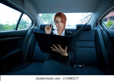 Beautiful young business asian with document in a car