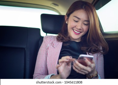 Beautiful young business asian woman smiling and using a smartphone in back seat of car. Successful Business Woman Using Mobile Phone to Navigate Internet Online Inside of Corporate Car.