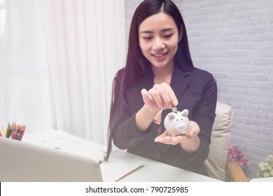 Beautiful young business girl saving money for holiday season, saving money concept