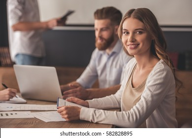 Beautiful young business lady is looking at camera and smiling during the conference in office