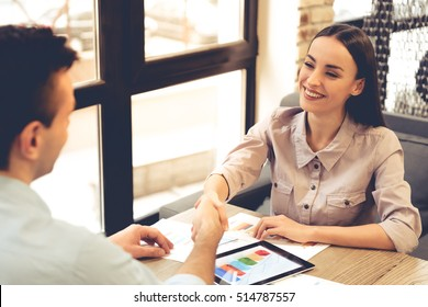 Beautiful young business partners are shaking hands and smiling while working in office