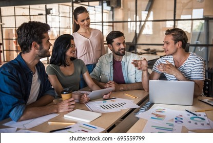 Beautiful young business people in casual clothes are using a laptop, talking and smiling while working in office