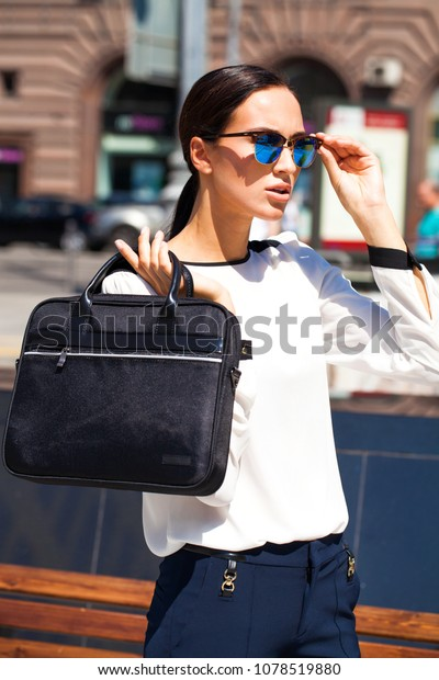 Beautiful young business woman in blue sunglasses