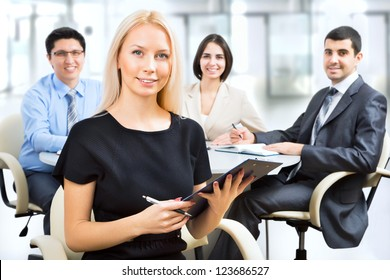 Beautiful young business woman with colleagues discussing in the background